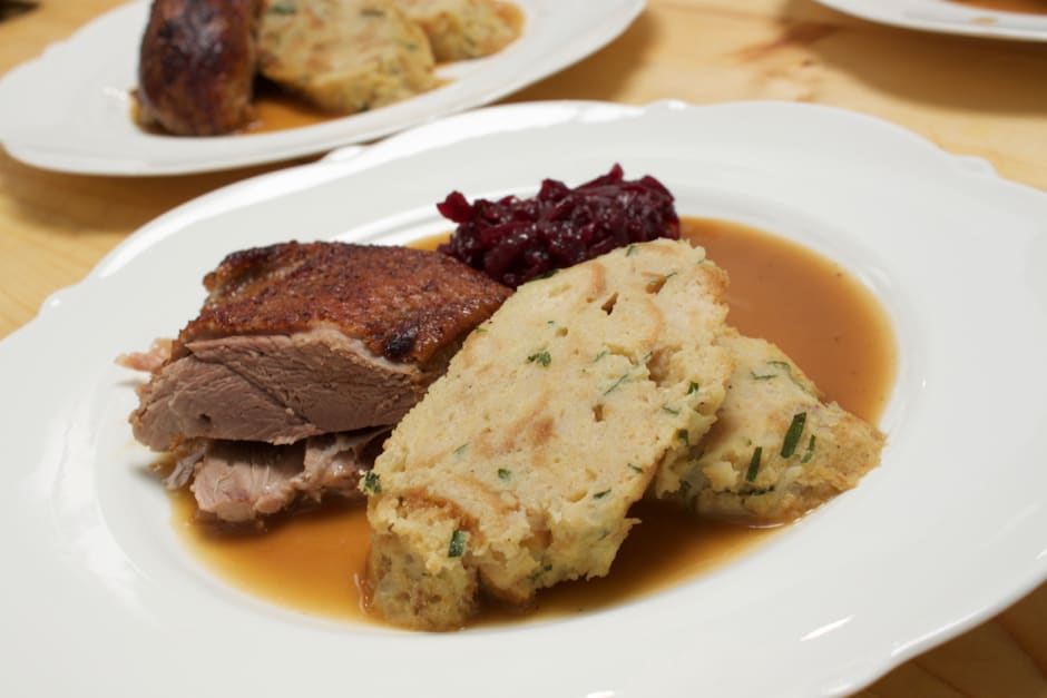 Roast goose served on a plate, here the breast, crispy. Served with napkin dumplings and red cabbage.
