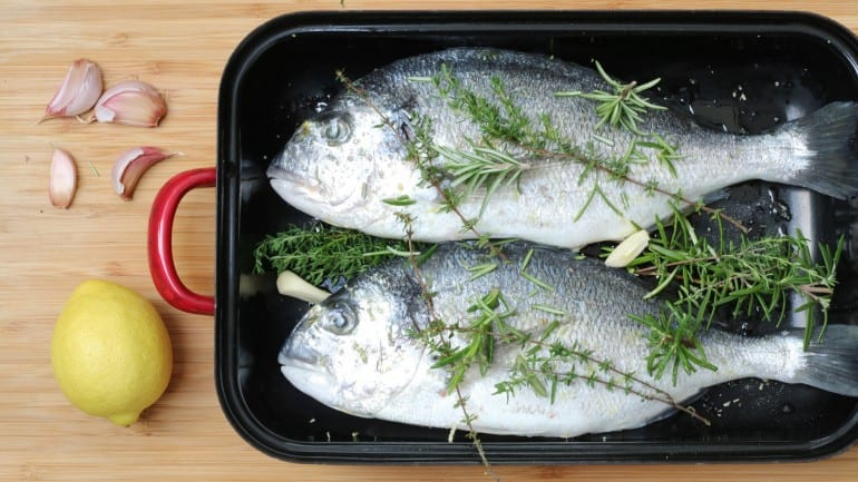 Prepare the sea bream for grilling with herbs and garlic
