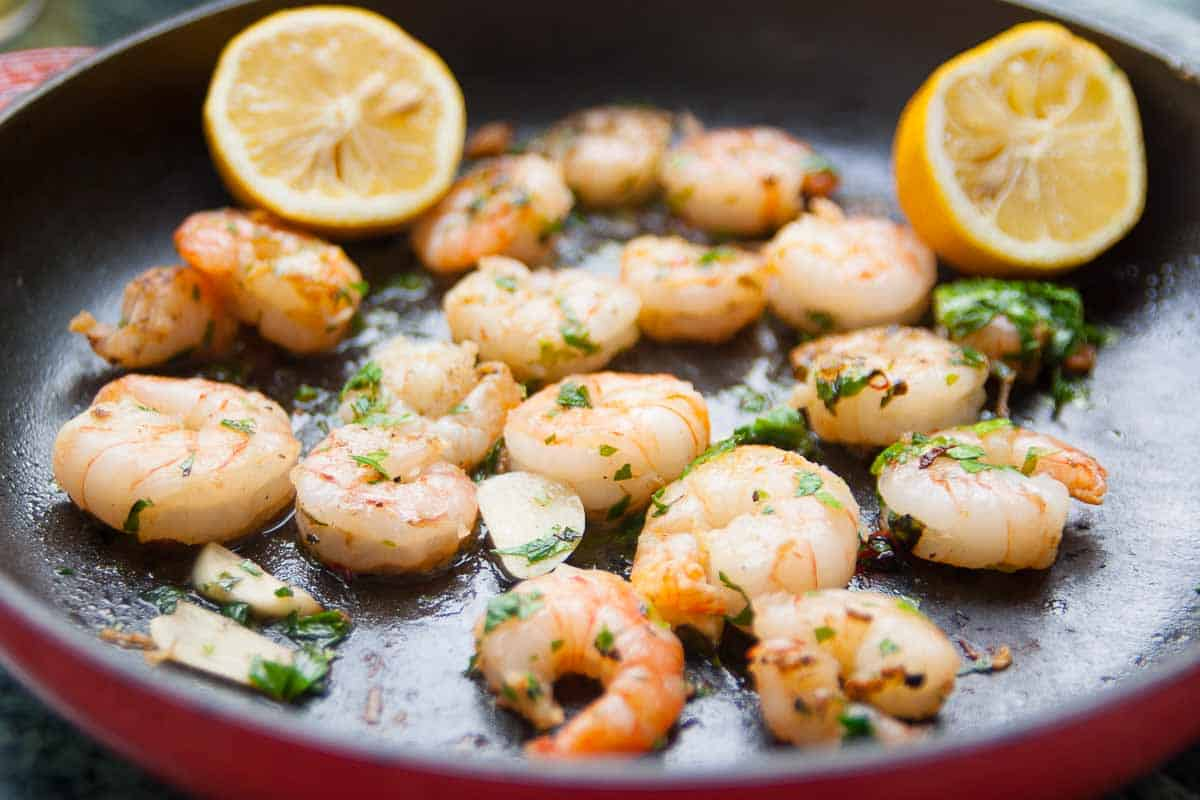 fried prawns with parsley and lemon juice in a pan
