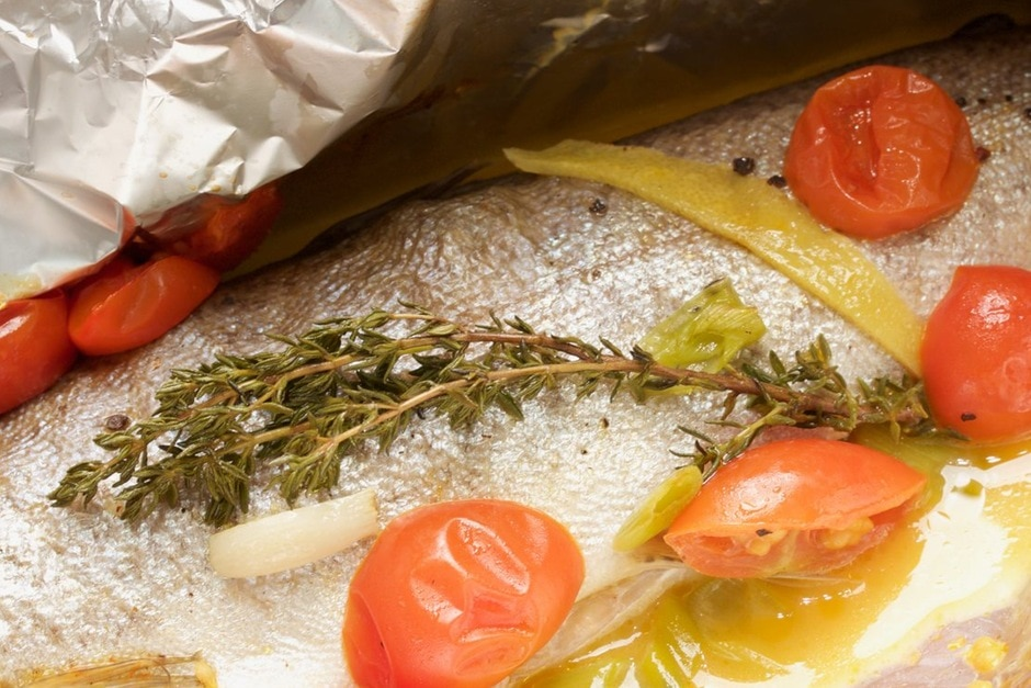 Preparing fish in aluminum foil Recipe Picture Trout in aluminum foil with vegetables and white wine sauce with thyme and tomatoes