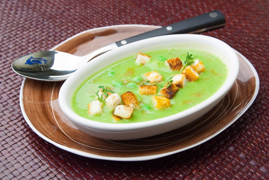 Pea soup served deliciously with bread cubes.