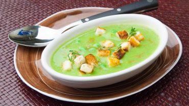 Pea soup served with bread cubes delicious.