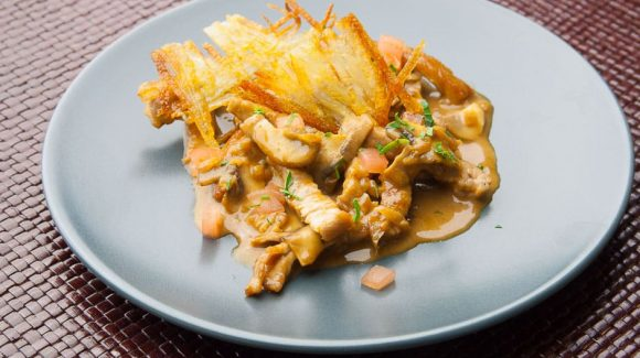 zurich ragout with tomato cubes and roesti on a plate
