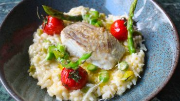 Lemon risotto served with asparagus, tomatoes and saithe.