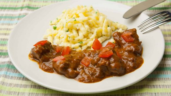 Beef goulash served with spaetzle, parsley and diced tomatoes