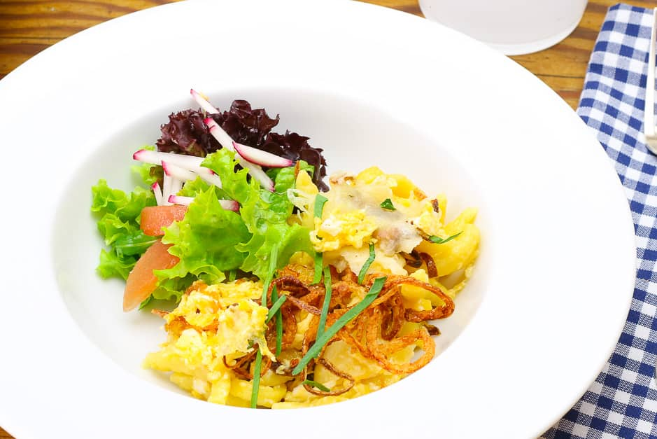 Cheese spaetzle close-up, served with salad.