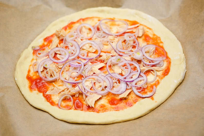 Spread the onions, finely chopped, on the tuna pizza.