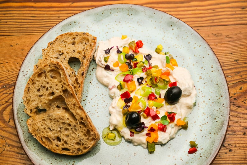 Tuna spread served with bread, vegetables and herbs.
