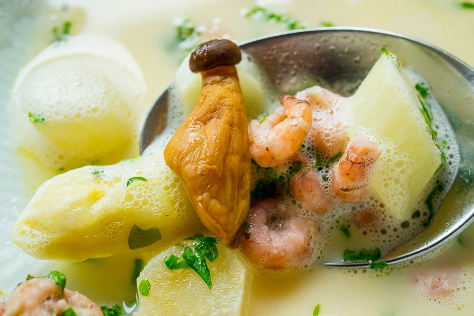 Cream of asparagus soup on a spoon with foam, asparagus tip and crabs.