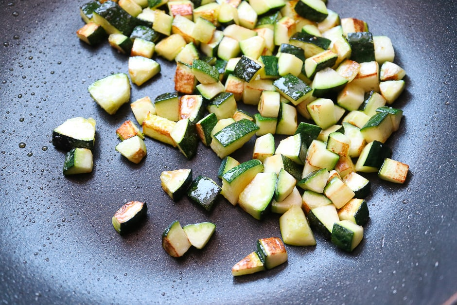 fried zucchini cubes in a pan.