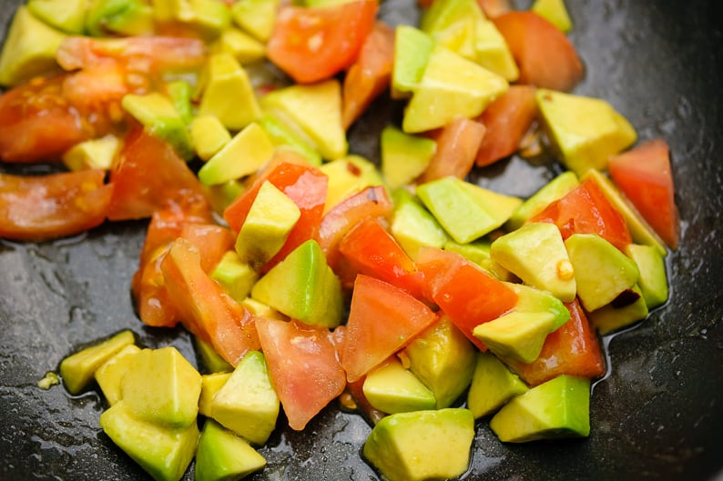 Tomatoes and avocado, diced when marinating with lemon juice and olive oil for couscous.