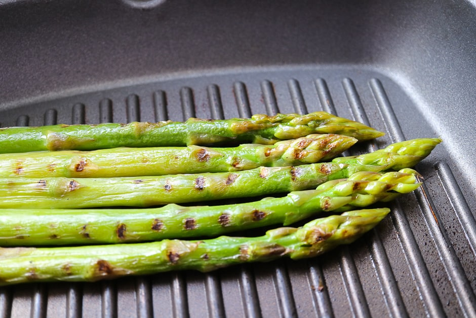 Grilling green asparagus in the pan.