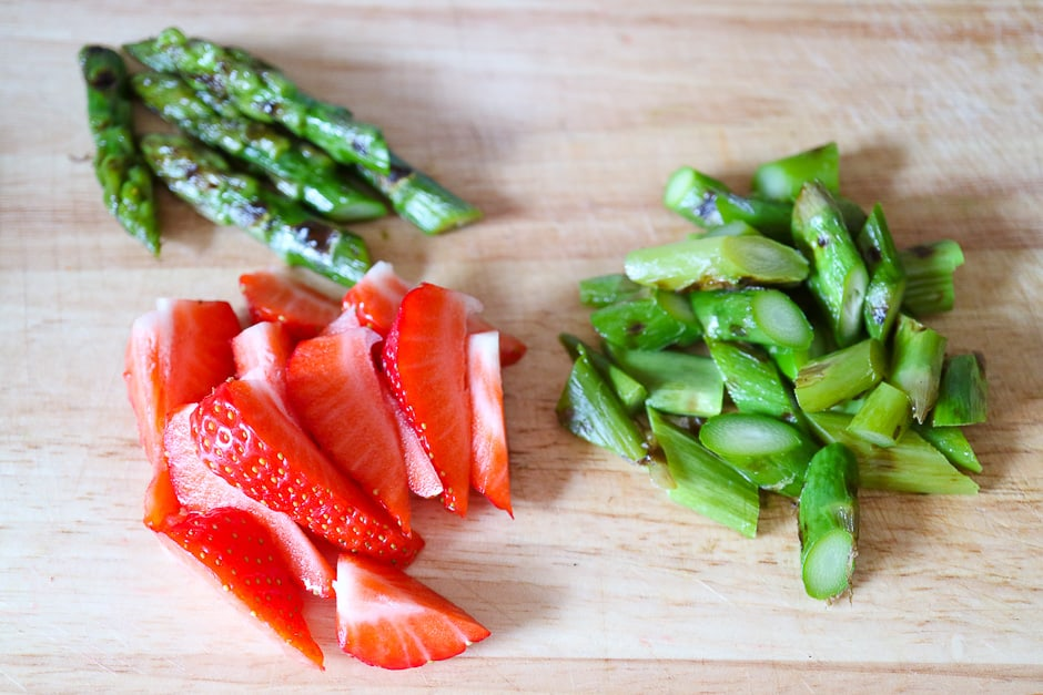 Cut asparagus and strawberries for salad.
