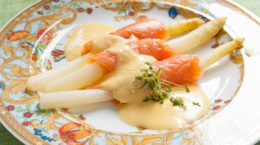 white asparagus with smoked salmon served with hollandaise sauce.