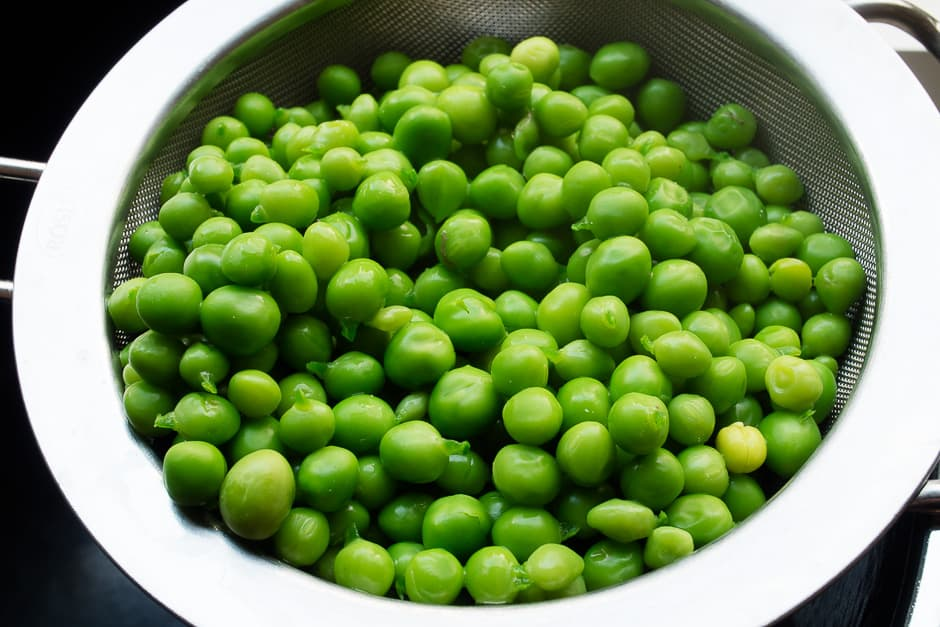Fresh, cooked, green peas on a kitchen sieve.