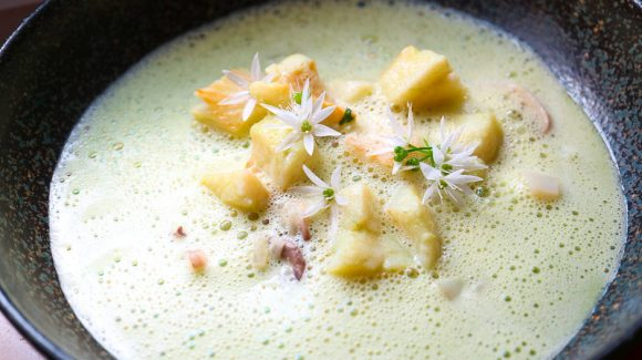 Wild garlic soup with fish and vegetables