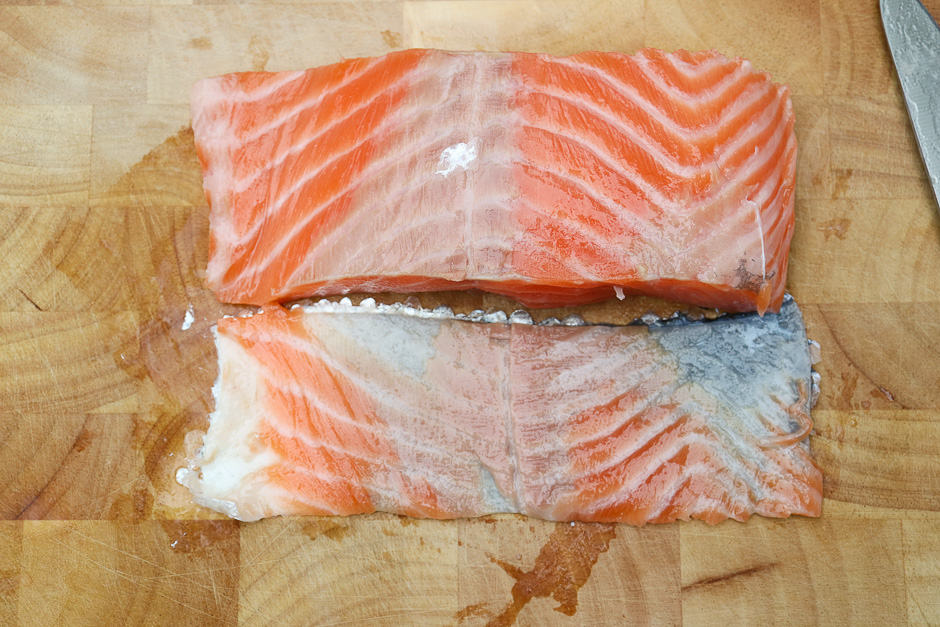 Skinless salmon fillet on a board next to the cut salmon skin with scales.