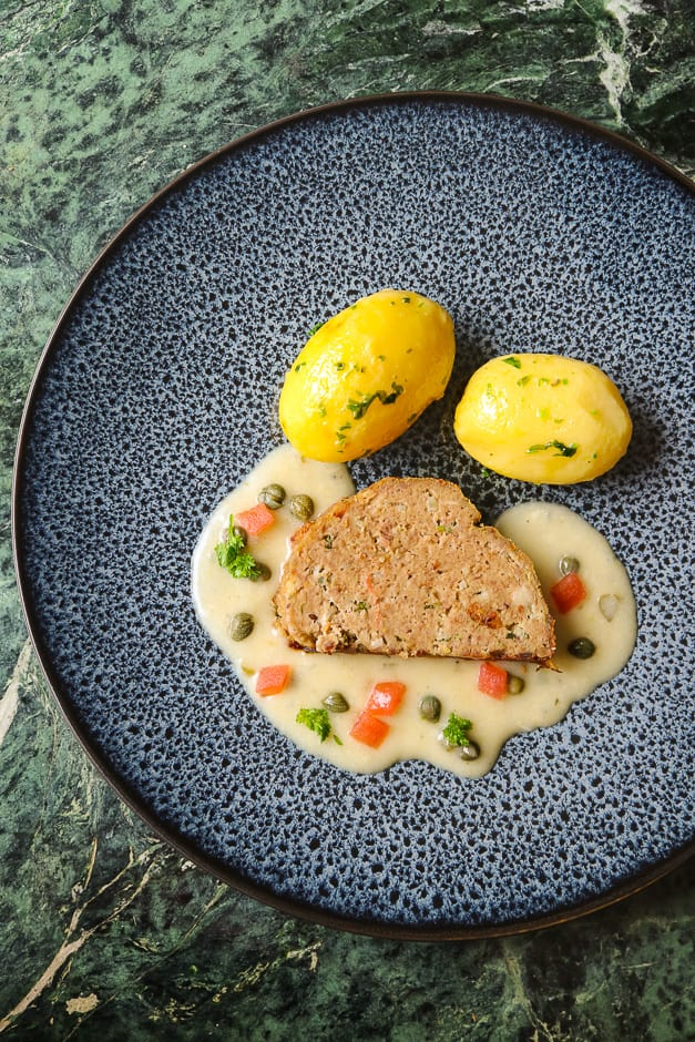 Meatloaf without filling, served with caper sauce, diced tomatoes, potatoes and parsley.