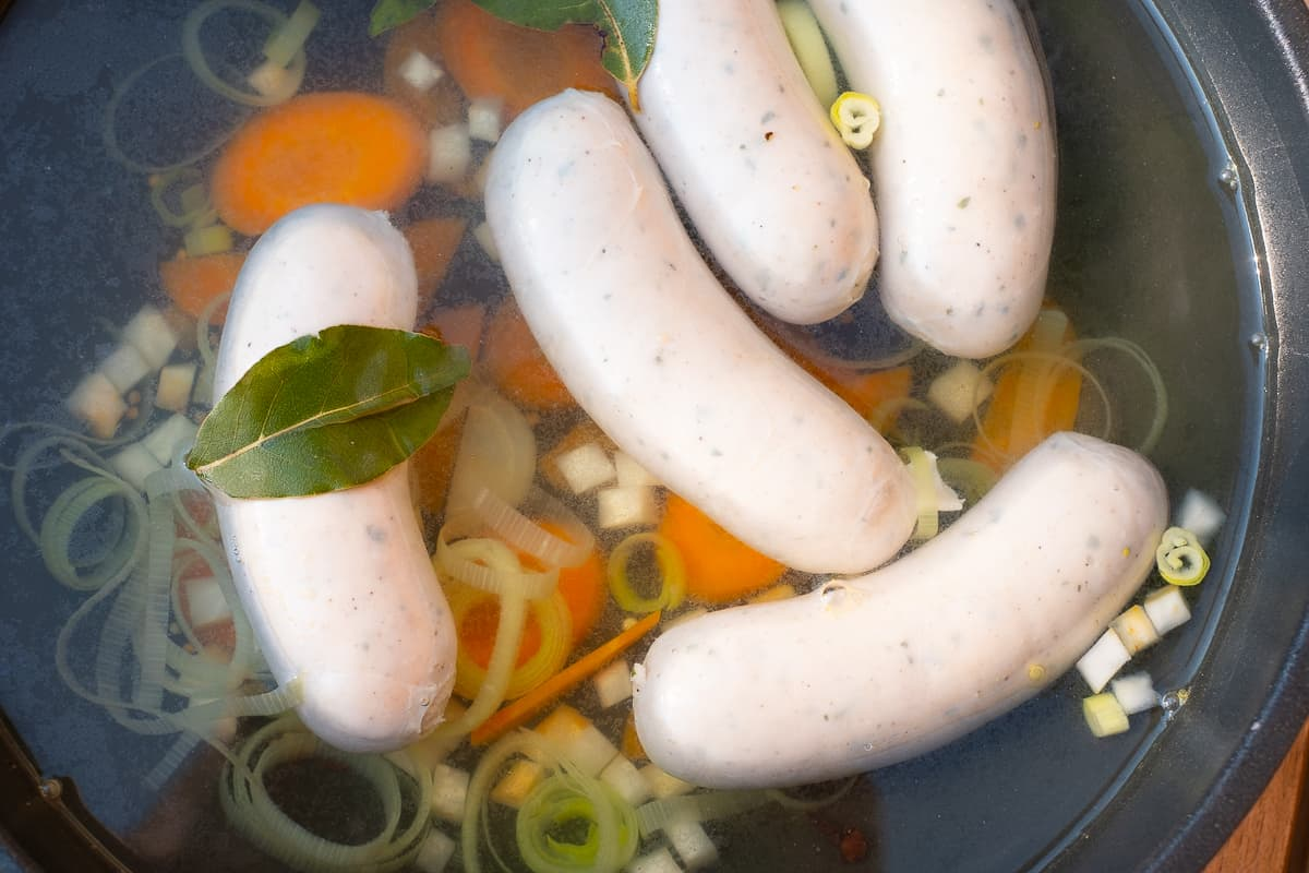 White sausages in the cooking stock