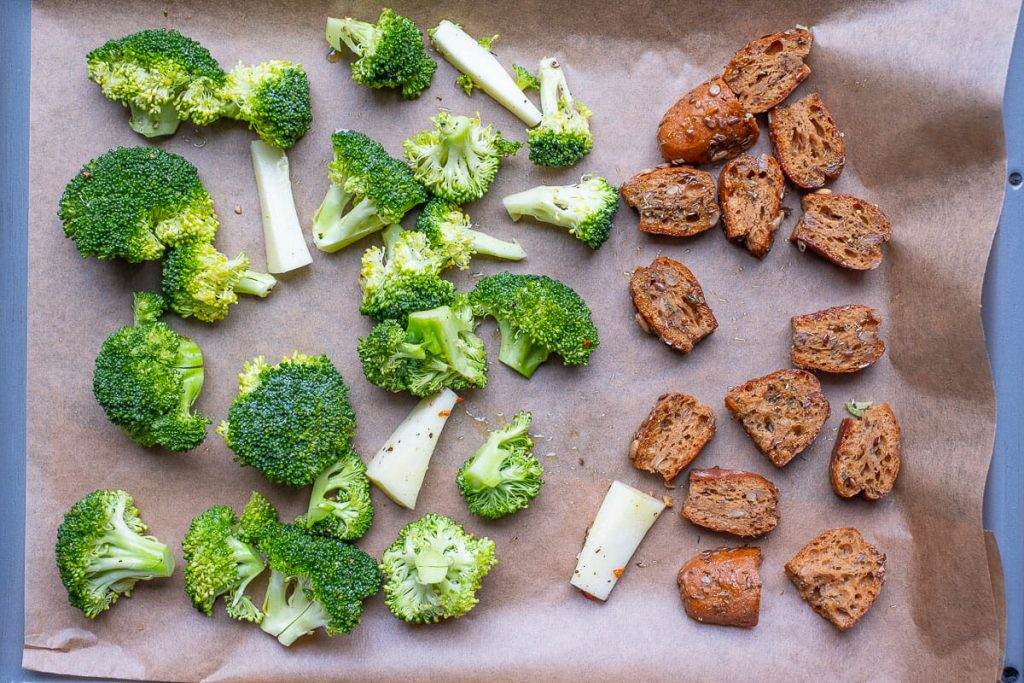 Raw broccoli and bread cubes on baking sheet