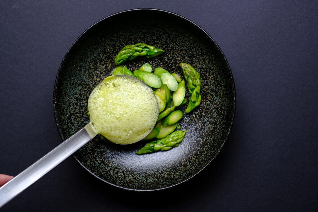 Put the asparagus soup in the plate