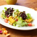 Starter colourful Lettuce Salad with glazed Apple Pieces, roasted Bread Croutons and Sea Buckthorn-Elder-Vinaigrette