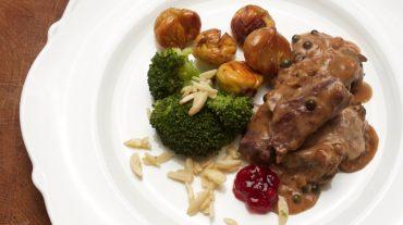 Hirsch mit Pfefferrahm-Sauce. Grüner Pfeffer in der Sauce als Beilagen Broccoli mit Mandeln und glasierte Maronen. Rezept Bild.