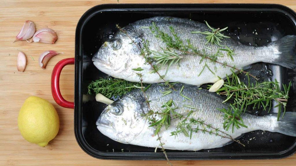 Prepare dorade for grilling with herbs and garlic