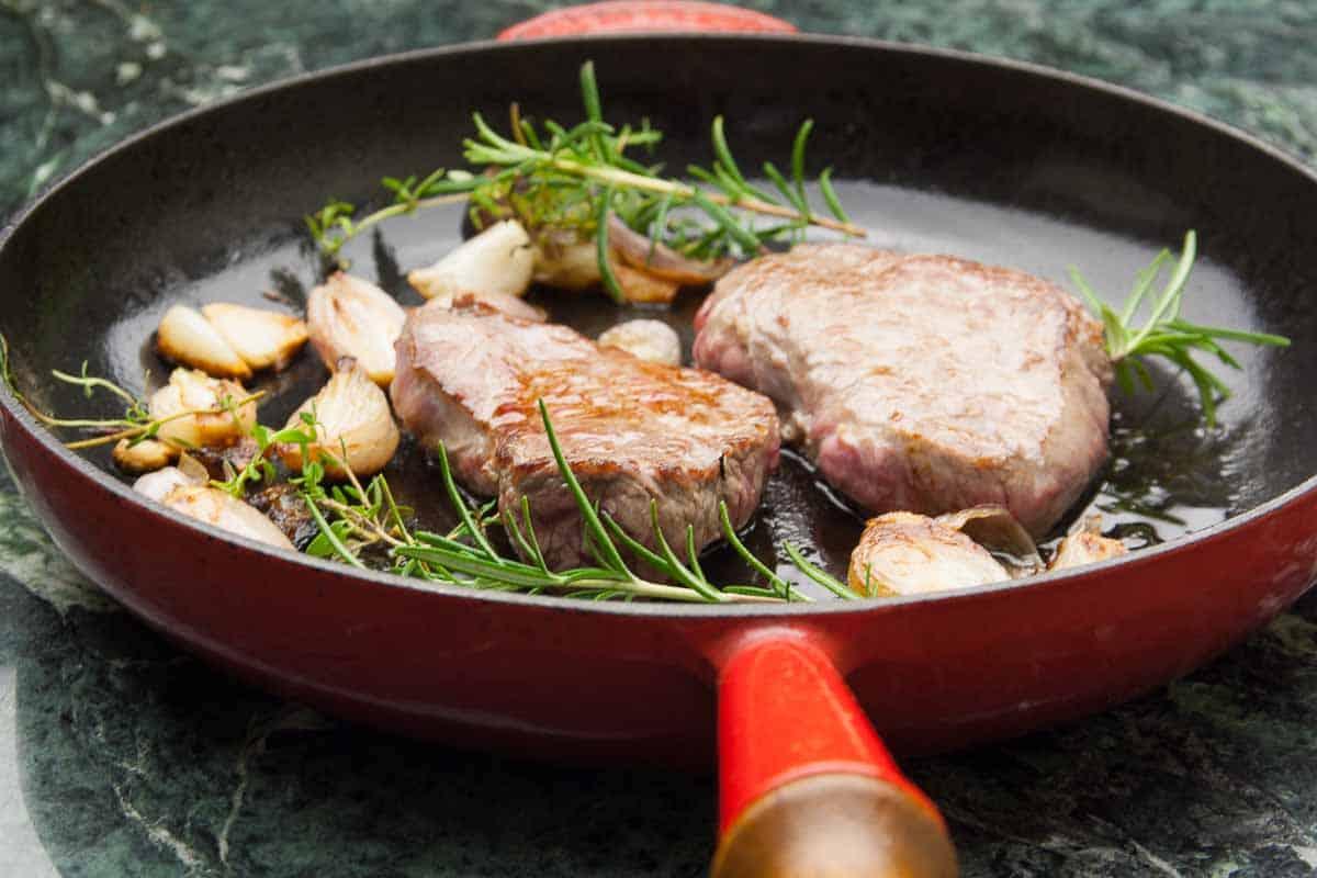 Kalbsschnitzel in der Pfanne mit Kräuter und Knoblauch.