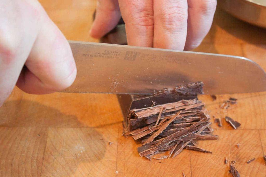 Dunkle Schokolade wird für die Wildsauce geschnitten.