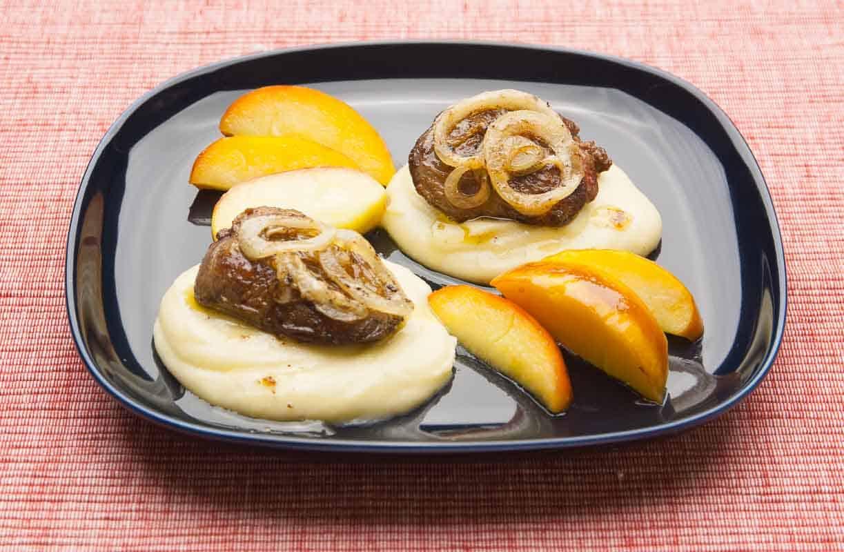 Kalbsleber Berliner Art oder Berliner Leber auf Kartoffelpüree mit Apfelspalten.
