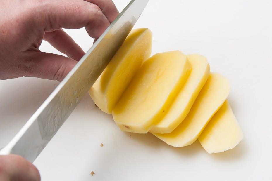 rohe, geschälte kartoffeln in scheiben schneiden