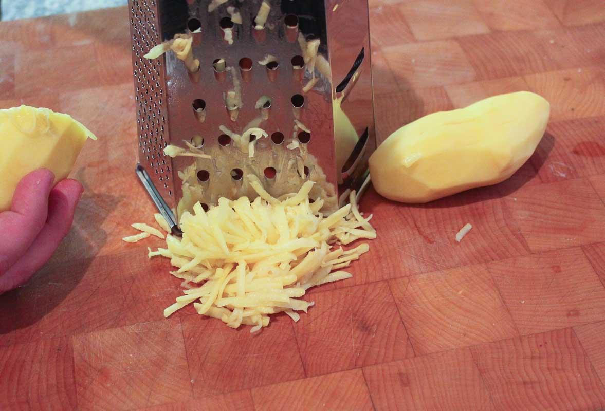 rohe kartoffeln für rösti und kartoffelpuffer grob reiben.