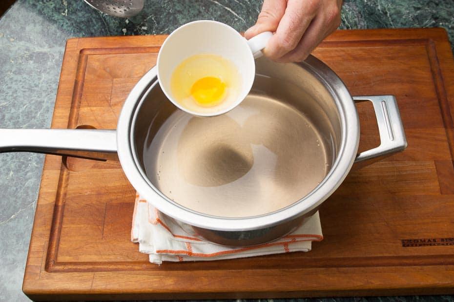 Ei pochieren, Wasser aufkochen, dann das Ei in das nicht mehr kochende Wasser einlaufen lassen.