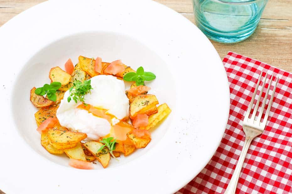 Ei pochiert mit Bratkartoffeln, Tomatenwürfel und Kräuter.