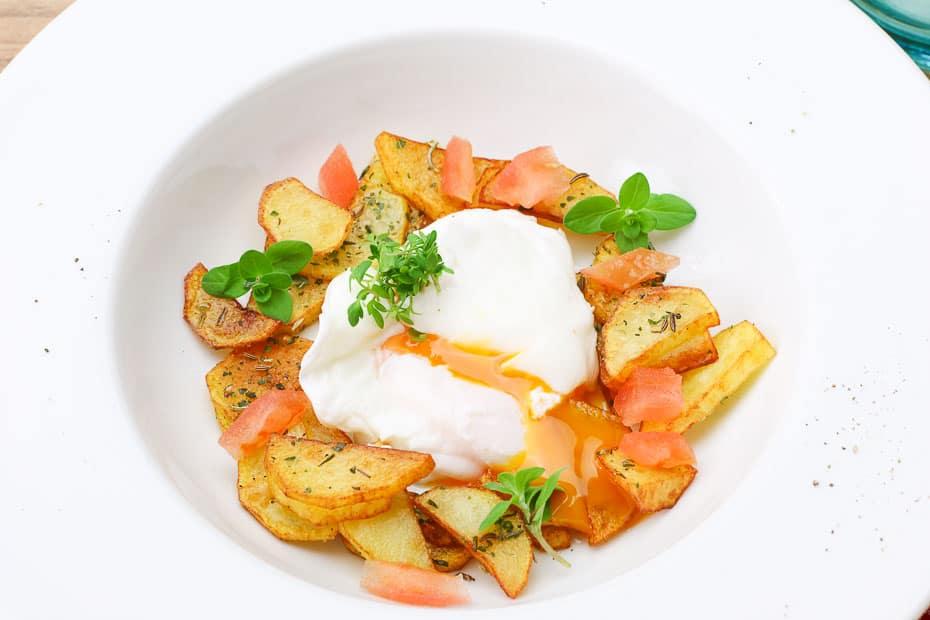 Pochiertes Ei mit deftigen Bratkartoffeln als Beilage.