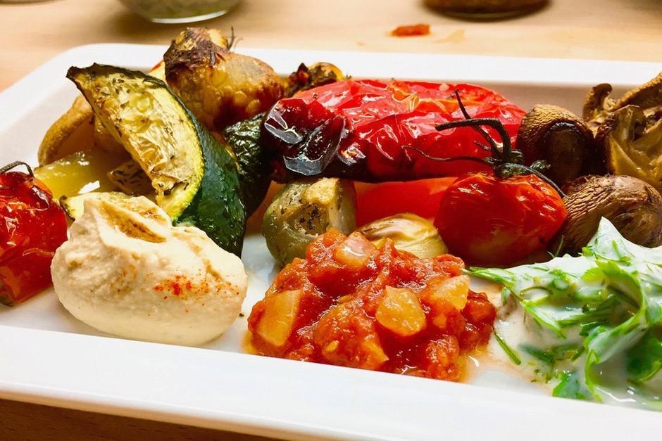 Ofengemüse lecker angerichtet mit humus, tomatenchutney und kräutersauce