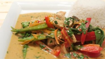 putengeschnetzeltes mit gemüse und kokosmilch im wok zubereitet mit reis serviert