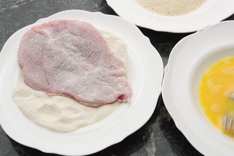 in mehl gewendetes schnitzel auf einem Teller umfeld panier-strasse