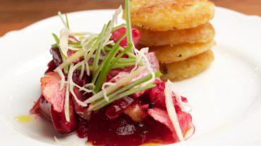 Heringssalat mit Apfel und rote Bete lecker angerichtet mit Meerrettich und Frühlingszwiebeln.