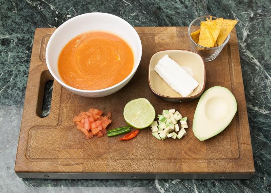 Kalte Tomatensuppe mit tomatenwürfel, Chili, Limette, Avocado, Schafskäse und Mais-Chips