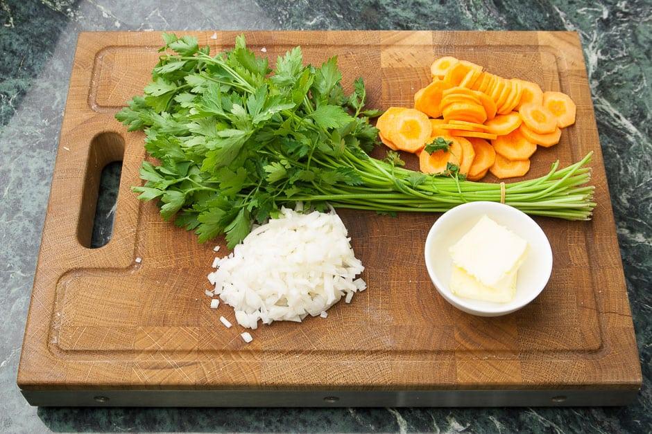 Zutaten für Karottencremesuppe und Karottensuppe auf einem Schneidebrett