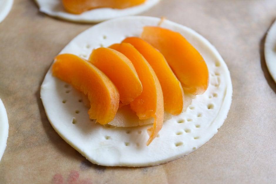Rohe Aprikosenspalten auf die Tartes legen