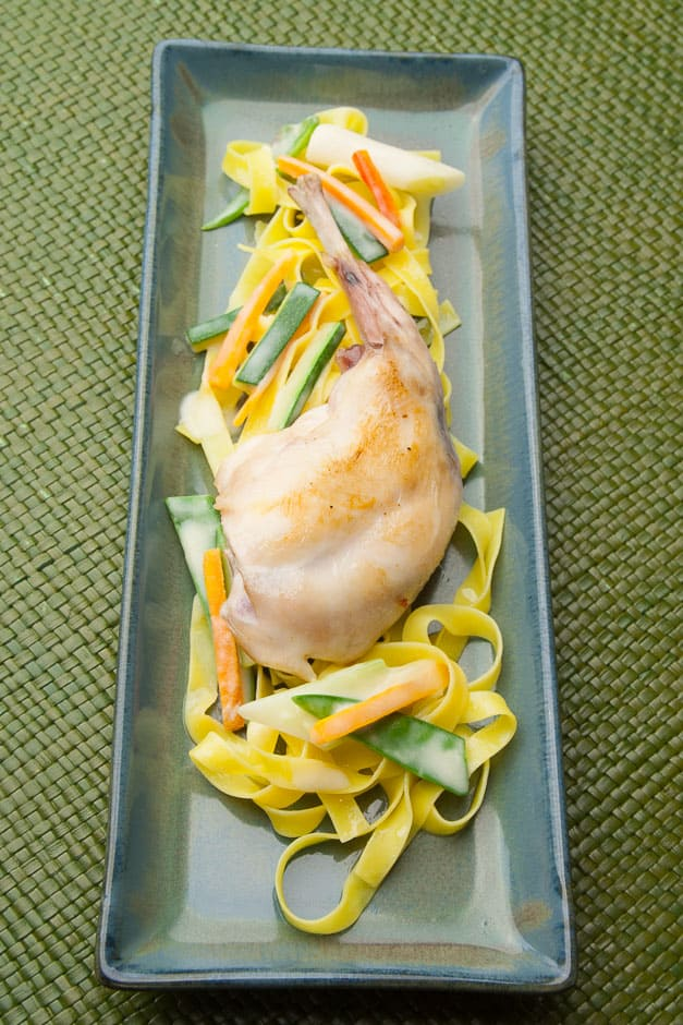 Braised rabbit legs with ribbon noodles and vegetables.