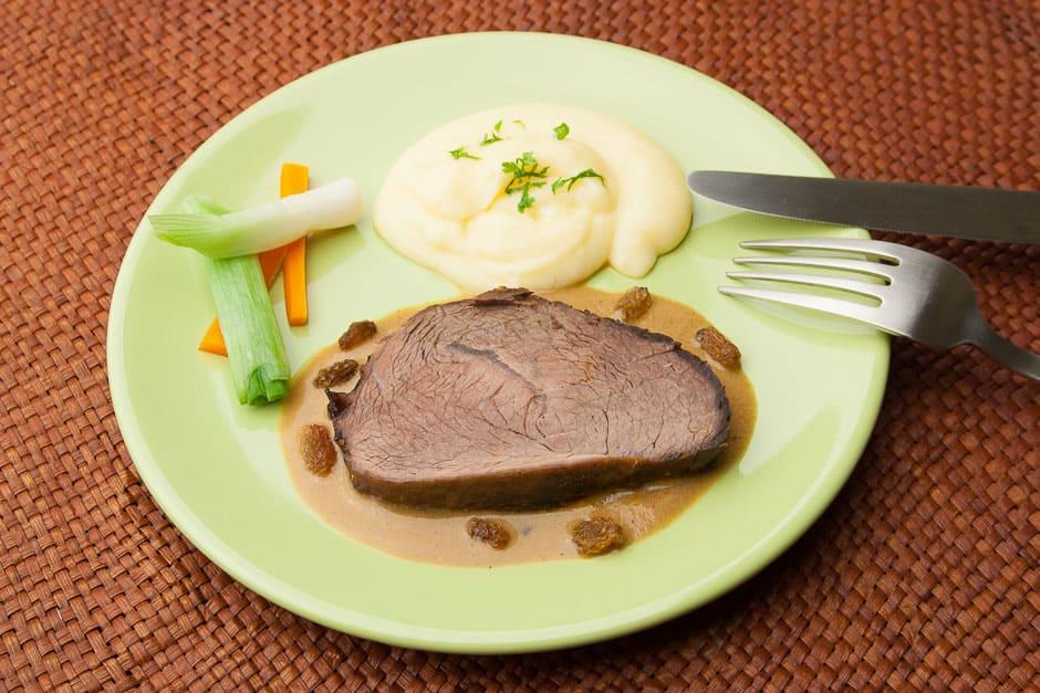 sauerbraten mit kartoffelpüree , gemüse und soße. ein klassisches deutsches gericht!