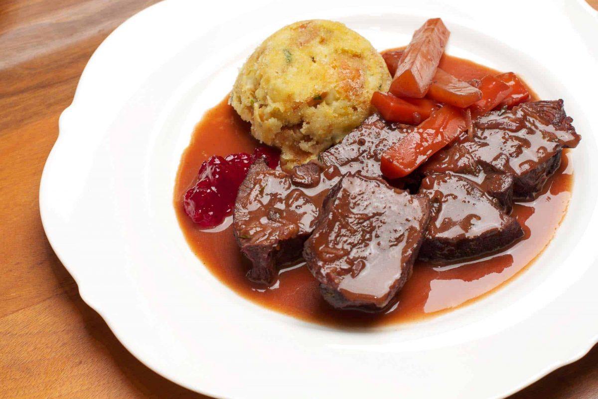 Hirschbraten Rezept Bild mit Knödel als Souffle, geschmorten Karotten, Soße und Preiselbeeren.