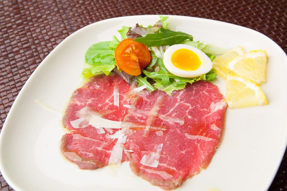 Carpaccio of beef fillet with parmesan, salad garnish, quail egg, lemon and tomato