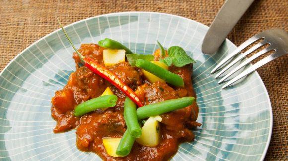 Lammgulasch Rezept angerichtet mit Kartoffeln und grünen Bohnen.