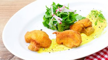 panierte Champignons knusprig gebacken als Vorspeise angerichtet mit Salat.