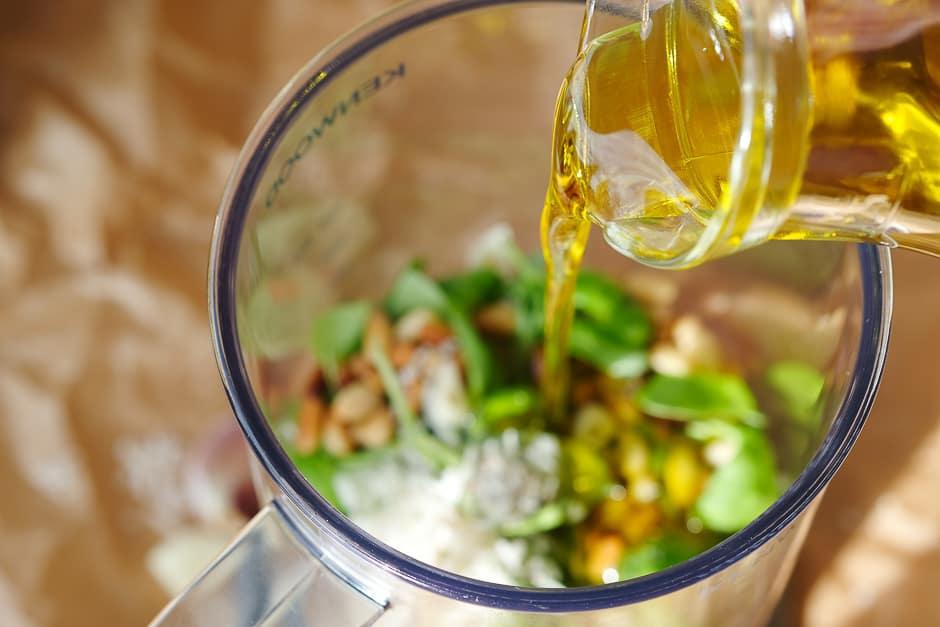 Olivenöl zu den Basilikumpesto-Zutaten gießen.